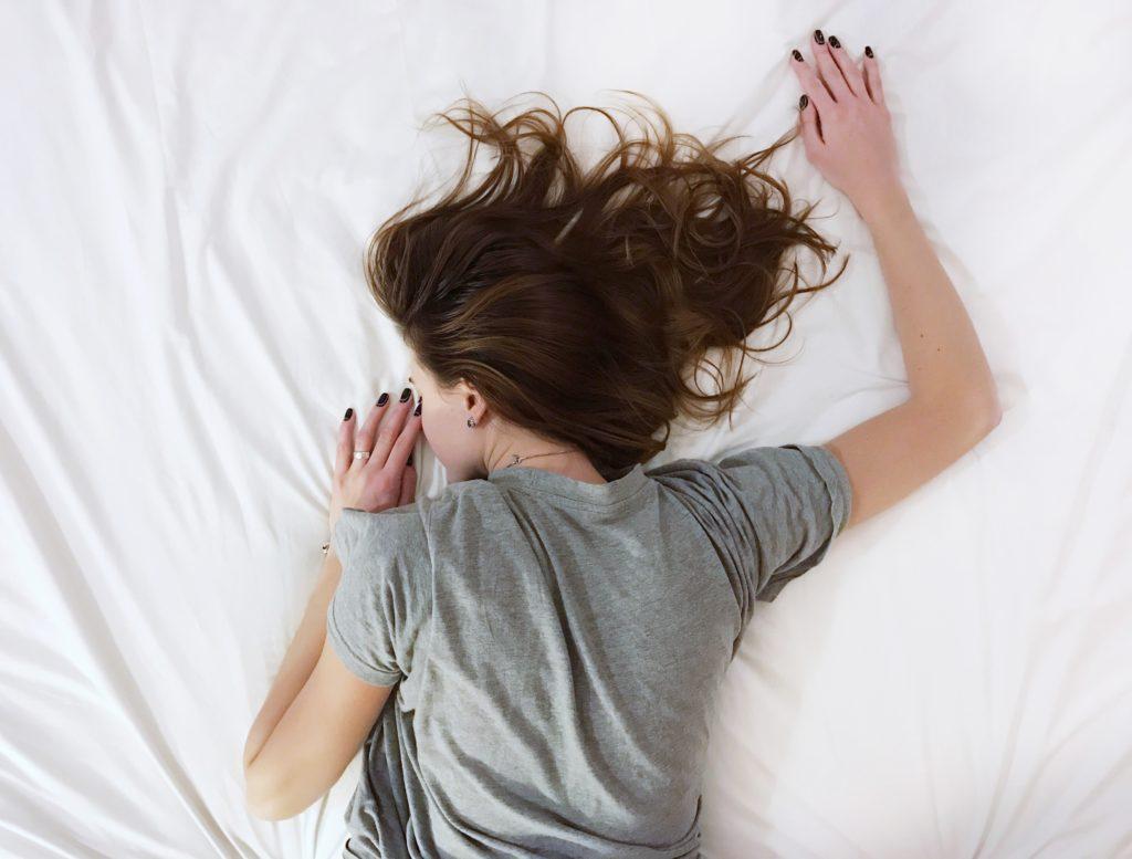 femme qui dort dans son lit - elle est fatiguée parce qu'elle mange pas assez de glucides