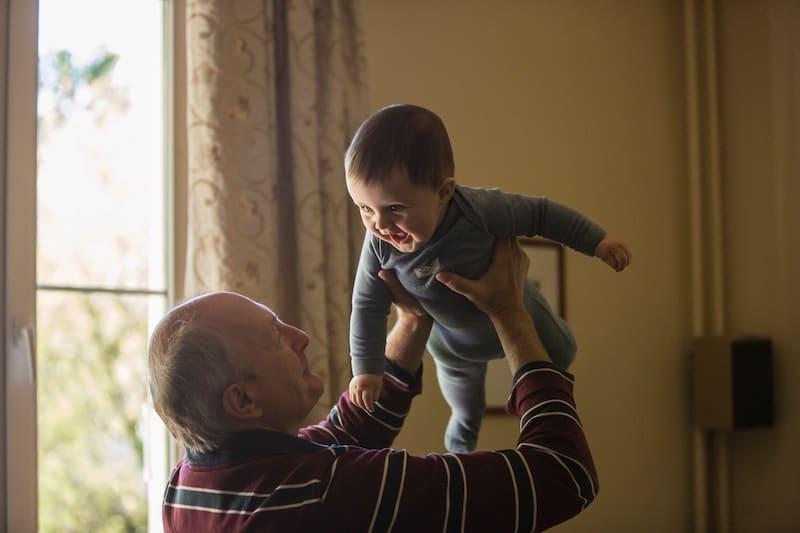 personne âgée qui porte un enfant